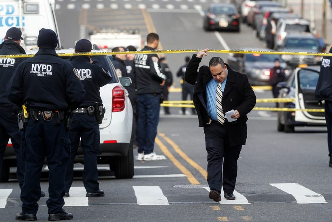 New York City police officers work the scene of a police-involved shooting outside the 41st precinct on Feb. 9, 2020.