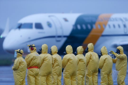 Soldiers wear protective suits during the arrival of Brazilians repatriated from Wuhan, China, the epicenter of the coronavirus, at the Annapolis Air Force Base, in Anapolis city, Goias state, Brazil, on Feb. 9, 2020. Dozens of Brazilians landed at the airbase in Goias, where they were to spend the next 18 days in quarantine.
