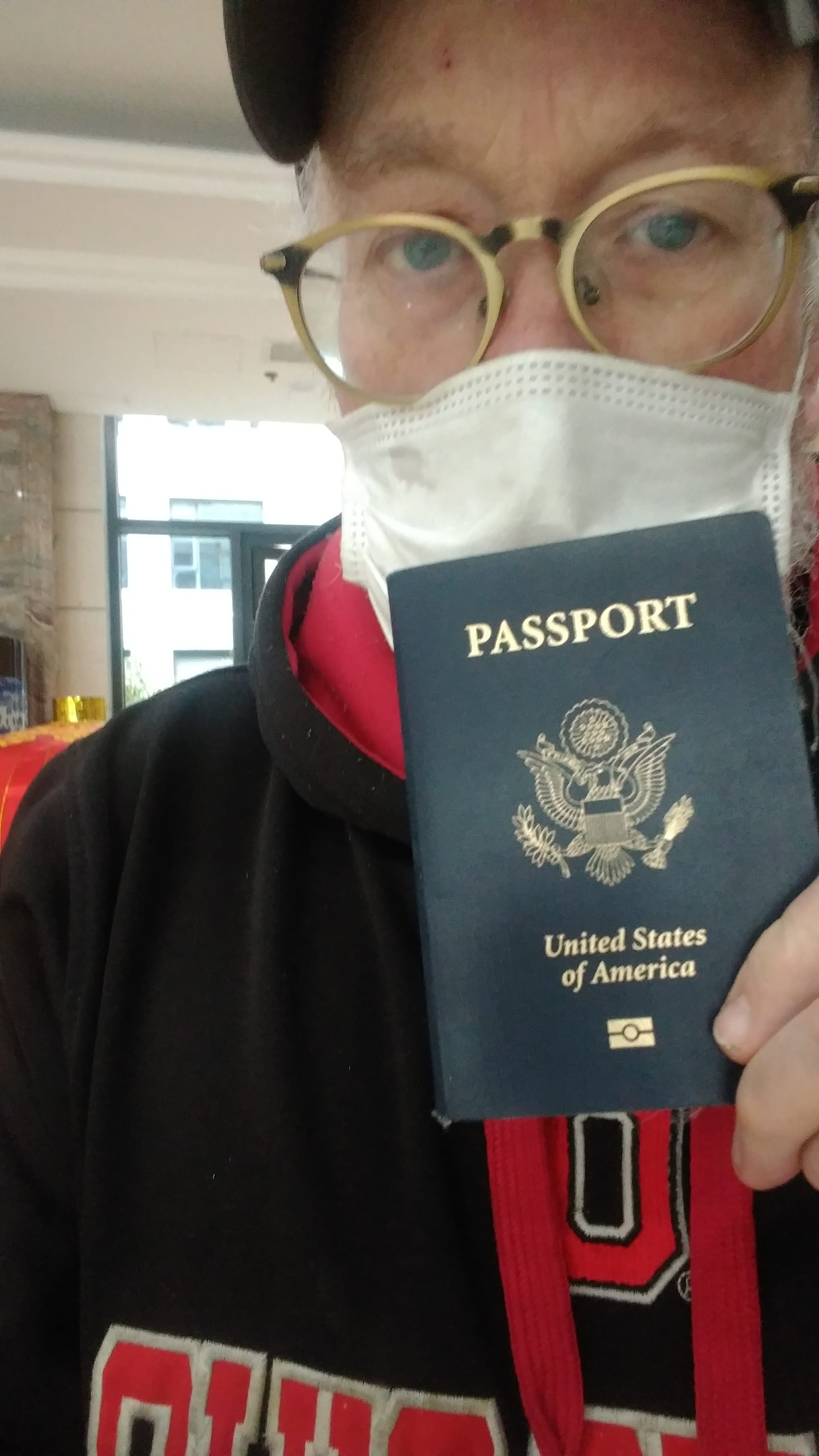 John McGory holds passport from the Wuhan Police, Feb 1, 2020.
