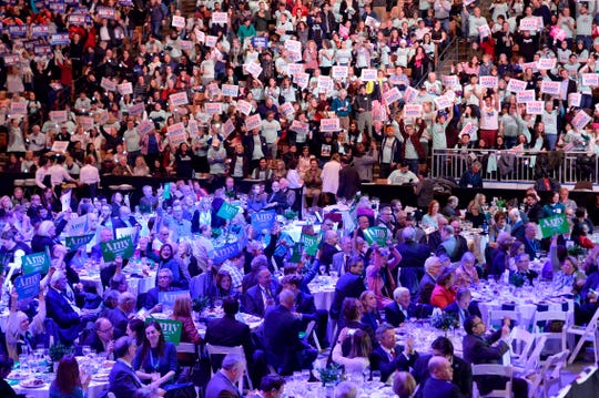 Attendees hold up signs during the Democratic Party's 61st Annual McIntyre-Shaheen 100 Club dinner at SNHU arena in Manchester, N.H., on Feb. 8, 2020.
