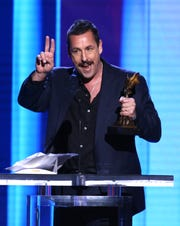 """Adam Sandler accepts the Best Male Lead award for """"Uncut Gems"""" at the Film Independent Spirit Awards."""
