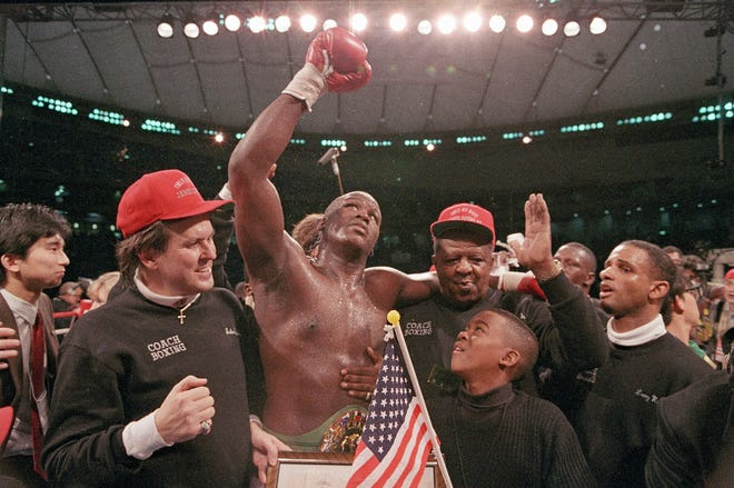 "FILE - In this Feb. 11, 1990, file photo, heavyweight boxer James ""Buster"" Douglas waves his gloved hand to the cheering crowd as he makes his way to the dressing room following a 10th-round knockout victory over Mike Tyson in a scheduled 12-round championship bout at the Tokyo Dome."