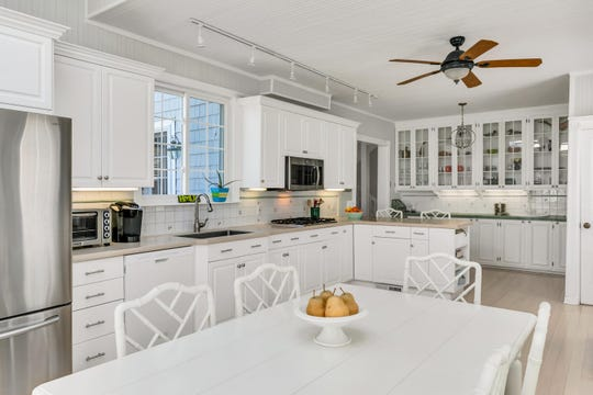 The kitchen offers custom cabinetry, recessed lights, and newer floors.