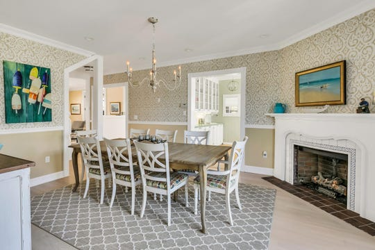 The dining room features crown molding and lavish wall paper.
