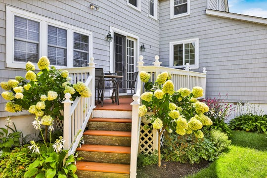 The backyard offers a deck and manicured greenery.