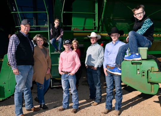 Galen and Clesta Boone, at far left, beside one of their cotton stripping machines with others in their family. The Boones have been chosen as Agriculture Family of the Year. On the ladder behind them is grandson Quinten Beaird, 9; beside him is the Boone's daughter Crystal Clinton, her husband Jason wearing the hat, their sons Brady, 13, (center) and Briley, 16. On the far right is Quinten's twin brother, Beckett.