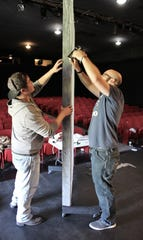 """David Goldie, left, and Michael Ingram staple material onto a frame in preparation for the opening of """"Midsummer."""""""