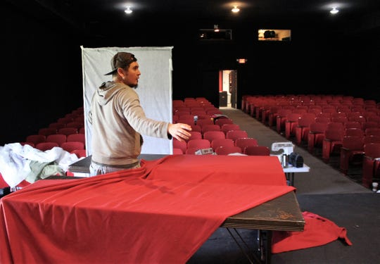 """David Goldie walks between tables to pull a cloth from its place, an action that is seen in """"Midsummer."""""""