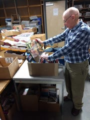 Jerry Wood sorts through book donations in the basement of the George F. Johnson Memorial Library in Endicott. He's been a member of the Friends of the George F. Johnson Memorial Library for 19 years.