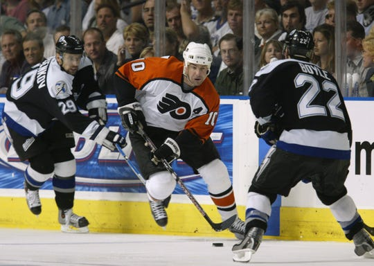 Left wing John LeClair, center, of the Philadelphia Flyers is pressured by Dmitry Afanasenkov and Dan Boyle (22) of the Tampa Bay Lightning in Game 2 of the NHL Eastern Conference Finals at the St. Pete Times Forum on May 10, 2004 in Tampa, Florida.