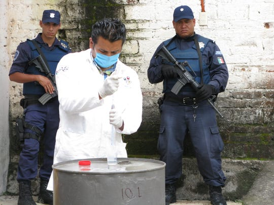 City police officers Gabriel Raya, left, and Rafael Trujillo stand guard as a federal forensics expert takes samples at a storehouse for chemicals used in making methamphetamine in Uruapan, Mexico on Aug. 28, 2009.