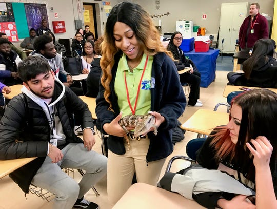 Shatiaa Burwell, an educator of Turtle Back Zoo in West Orange, showing a skink to zoology students at Linden High School. Zoo representatives visited to thank students for raising money to help animals devastated by wildfires in Australia.