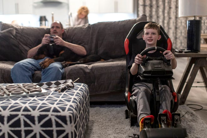 Keegan Sobilo, 12, drives on the simulator, races against his father Roman Sobilo, who plays with a game console in the living room at their home in New Baltimore, Wednesday, Feb. 5, 2020.