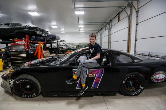 Keegan poses for a photo with his race car in the garage of his home in New Baltimore in February.