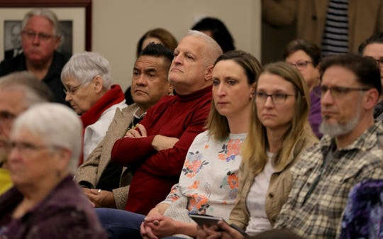 Audience members listen to a speaker at Saline City Hall on Sunday.