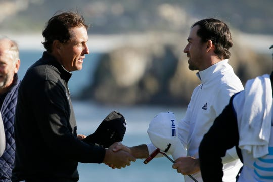 Nick Taylor, right, of Canada, is greeted by Phil Mickelson on the 18th green of the Pebble Beach Golf Links after winning the AT&T Pebble Beach National Pro-Am golf tournament Sunday, Feb. 9, 2020, in Pebble Beach, Calif. (AP Photo/Eric Risberg)