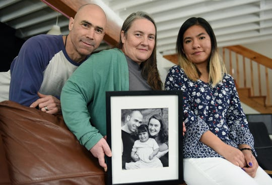 Katie Sander, center, and her husband Jeff, left, and their adoptive daughter, Daniela, hold a photo when Daniela was 4 inside their home.