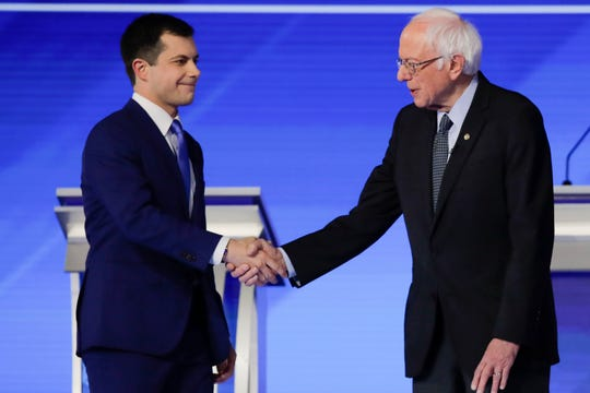 Democratic presidential candidates former South Bend Mayor Pete Buttigieg and Sen. Bernie Sanders, I-Vt., shake hands on stage Friday, Feb. 7, 2020, before the start of a Democratic presidential primary debate.