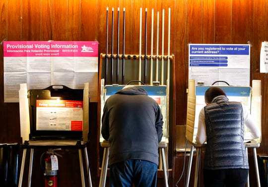 In this Nov. 8, 2016, file photo, residents of Chicago' 33rd Ward mark their ballots at Marie's Golden Cue pool hall. An embarrassing mistake in Illinois' automatic voter registration system could mean deportation, criminal charges or both for a handful of people who cast recent ballots.
