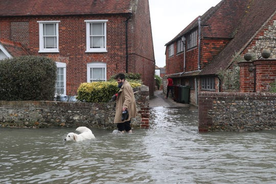 A man walks with a dog in flood water, in the aftermath of Storm Ciara, in Bosham, Sussex , England, Monday Feb. 10, 2020.