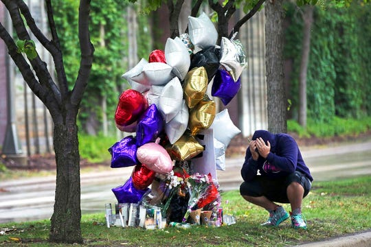 In this Sept 9, 2019, file photo, Shawn Price mourns at a memorial in Richfield, Minn. near where police shot and killed Brian J. Quinones who had streamed himself live on Facebook during a police chase after he apparently emerged from his car holding a knife and refused their commands to drop it Saturday night.