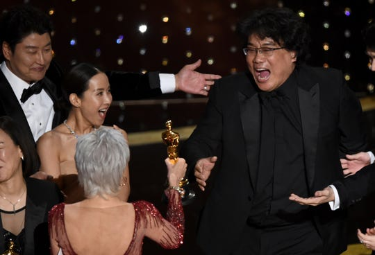 """Bong Joon Ho, right, reacts as he is presented with the award for best picture for """"Parasite"""" from presenter Jane Fonda at the Oscars on Sunday, Feb. 9, 2020, at the Dolby Theatre in Los Angeles. Looking on from left are Kang-Ho Song and Kwak Sin Ae."""