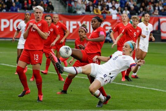 U.S. midfielder Julie Ertz kicks the ball past Canada defender Kadeisha Buchanan during the second half of a CONCACAF women's Olympic qualifying soccer match Sunday. The U.S. won 3-0.