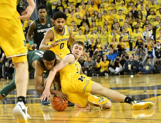 Michigan guard Franz Wagner, right, and Michigan State forward Aaron Henry, left, go for the ball while Michigan guard David DeJulius (0) and Michigan State guard Rocket Watts, left rear, look on in the first half.