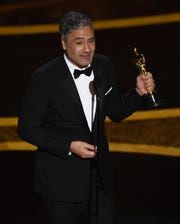 "Taika Waititi accepts the award for best adapted screenplay for ""Jojo Rabbit"" at the Oscars on Sunday, Feb. 9, 2020, at the Dolby Theatre in Los Angeles."