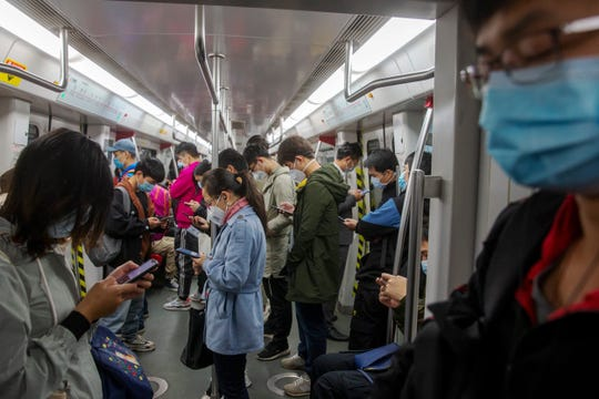Masked commuters ride on a subway train to their workplaces in Guangzhou in south China's Guangdong province, Monday, Feb. 10, 2020. China reported a rise in new virus cases on Monday.