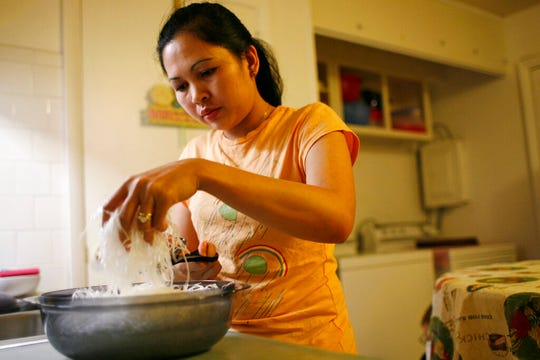 In this Nov. 21, 2007, photo, Elizabeth Keathley, a Philippine citizen in the U.S. on a marriage visa, prepares dinner in Bloomington, Ill. She applied for a driver's license and was sent a voting registration card. She voted in 2006. In processing her green card, immigration authorities discovered she had voted, and she was ordered removed. However, judges determined she did not falsely represent herself, allowing her to stay.