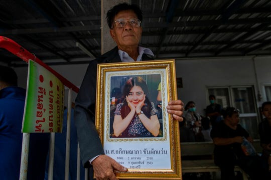Khunpol Khanpakwan holds a portrait of his daughter Apiksanapa Khanpakwan outside a hospital morgue in Nakhon Ratchasima, Thailand, Monday, Feb. 10, 2020. It's still unclear how a Thai soldier managed to steal heavy weapons from an army base which he then used to kill 29 people and hold off security forces for almost 16 hours while he was holed up in a popular shopping mall.