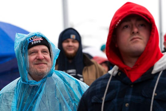 Trump supporters watch a giant video screen displaying President Donald Trump as they waits outside the venue where Trump will hold a campaign rally in the evening, , Monday, Feb. 10, 2020, in Manchester, N.H.