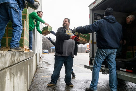 Bob Barnett, center, gets help from volunteers as they pack his rented U-Haul truck with cookies at Belmont Moving & Storage in Evansville, Ind., Monday, Feb. 10, 2020. His wife Heather Barnett leads Troop 484, which sold about 8,000 boxes of cookies last year.