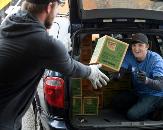 Volunteer John Davenport, left, helps his Vectren co-worker Michael Blanchard load up a car with Girl Scout Cookies at Belmont Moving & Storage in Evansville, Ind., Monday, Feb. 10, 2020. Thousands of cookie boxes were stored and sorted at the facility and troops were assigned times to pick up their orders on Monday and Tuesday.