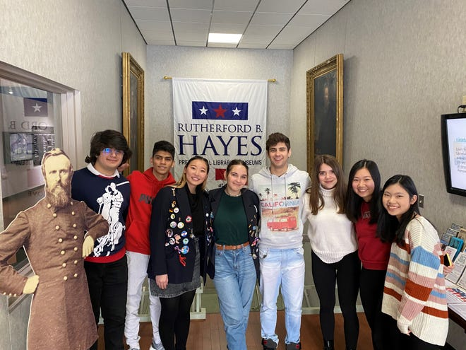Exchange students from eight countries snap a photo with US President Rutherford B. Hayes cutout.