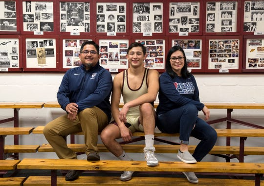 Jesse Sr. and Jennifer Martinez sit with their son Jesse in the wrestling room at Riverdale High School on Jan. 27, 2020.