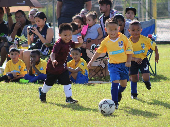 Players from the Tumon Typhoons FC and Community First/Days Inn Dededo Soccer Club play in an opening day U6 division match of the Triple J Auto Group Robbie Webber Youth Soccer League Saturday at the Guam Football Association National Training Center.