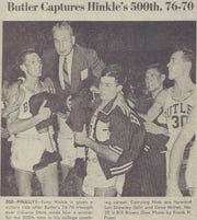 Lon Showley (left) helps lift Tony Hinkle after the Butler coach's 500th win.