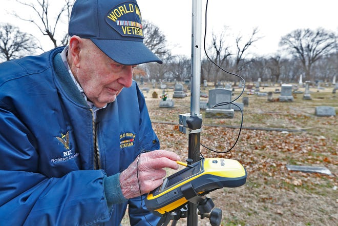 Bob Vollmer, 102, checks a GPS reading as he surveys in the Riverside Cemetery in Clinton, Indiana on Wednesday, Feb. 5.. It was his last day at work before retiring after working for the Department of Natural Resources for 57 years.