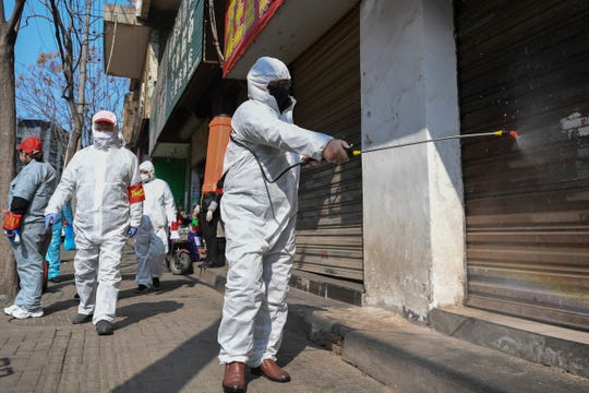 In this photo released by Xinhua News Agency, workers disinfect closed shop lots following the coronavirus outbreak in Jiang'an District of Wuhan in central China's Hubei Province on Monday.