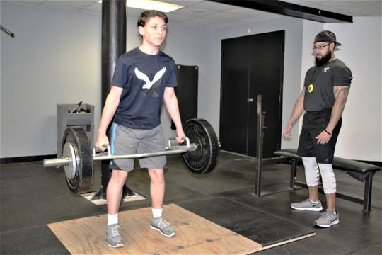 Taylor Gundy, right, a trainer at Phase 6 Strength and Performance in Marion, guides Nygil Horn, left, a club hockey player who is a sophomore at River Valley High School, through his dailyworkout. Horn plays for the Northeast Storm of the Ohio Scholastic Hockey League.
