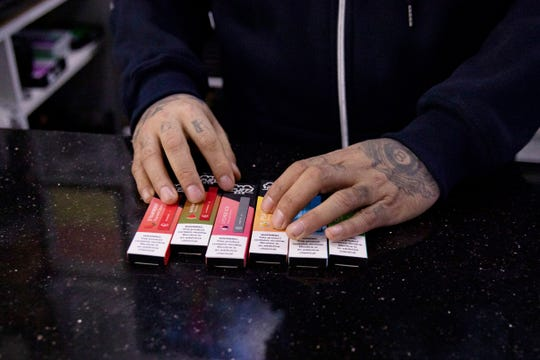 In this Jan. 31 photo, a vape shop manager shows Puff Bar flavored disposable vape devices at a store in the Brooklyn borough of New York.