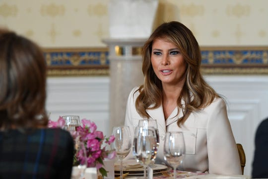 First lady Melania Trump sits down at her table after speaking during a luncheon with governors' spouses in the Blue Room of the White House on Monday, Feb. 10, 2020.