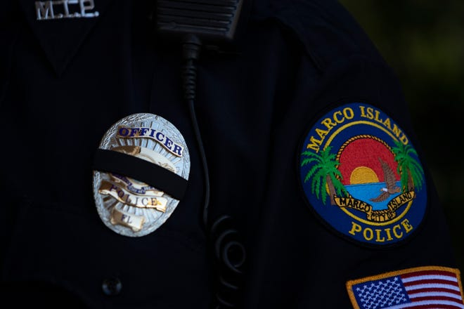 A Marco Island police officer wears a mourning band in February.