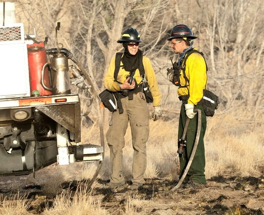 Lisa Bartley in firefighting gear with David Hall and engine  B140 on an assignment. Notice burned ground cover.