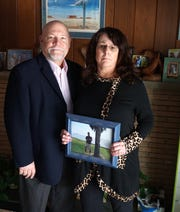 Ken and Katherine Massey stand in their Farmington Hills home with a portrait of Katherine's late son Graham E. Smith. The couple have began the Graham E. Smith Memorial Fund to honor him soon after he fatally shot himself on May 9, 2011 – the day after Mother's Day.