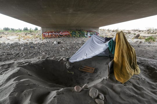 A hole dug in the sand serves as a makeshift shelter under the Orange St. bridge over the Santa Ana River in Redlands, February 9, 2020.