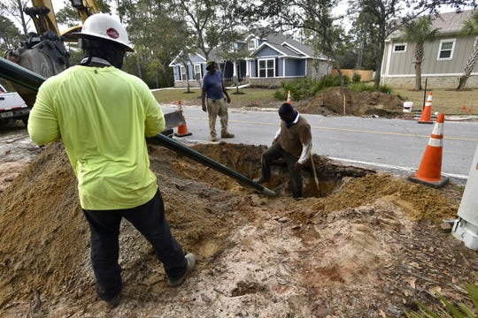 Workers from the Talcon Group install an underground sewer pipe at Innerarity Island on Monday.