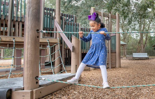 Ava Frazier, 5, of Pace, concentrates as she crosses a rope bridge at Benny Russell Park in Pace on Monday, Feb. 10, 2020.  This park is slated to get approximately $4 million in upgrades including a splash pad and walking trails.